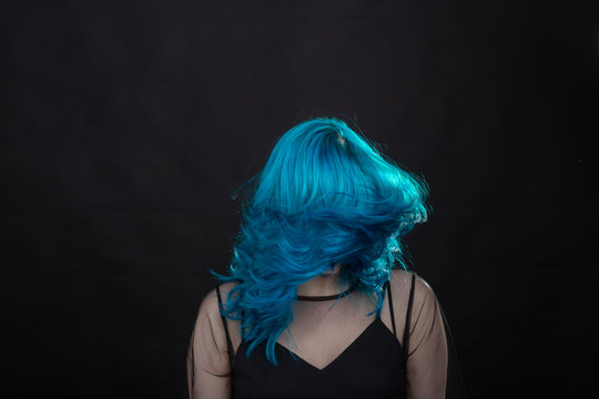 people, fashion and hair concept - close-up portrait of young woman in black dress with blue hair on black background