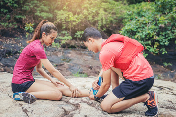 Woman runner has twisted ankle injury for trail runner on mountain take care by her friend