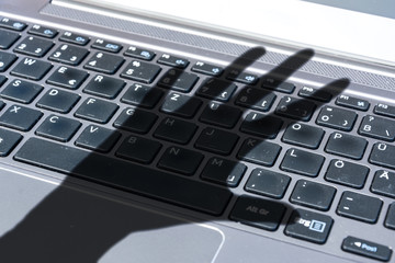 Dark shadow of a hand reaches for computer keyboard symbolizing cyber crime