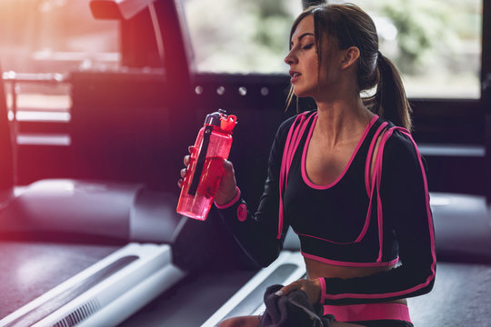 Girl drinking water in gym after workout. Lens flare