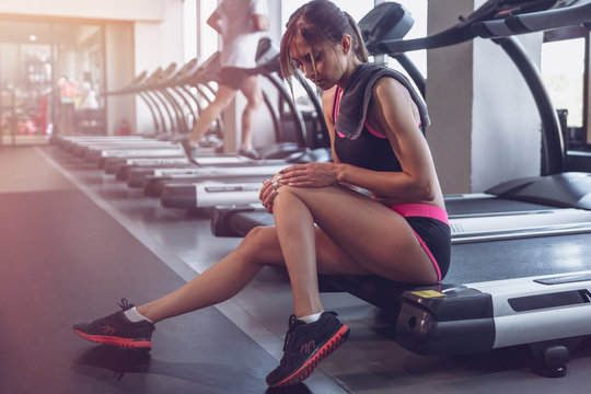 Woman getting a knee injury in the gym. The muscle sprain