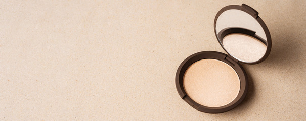 Face powder on the sand background. Summer cosmetics. Highlighter.Copy space.