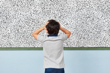 Child with dyslexia in front of whiteboard in elementary school