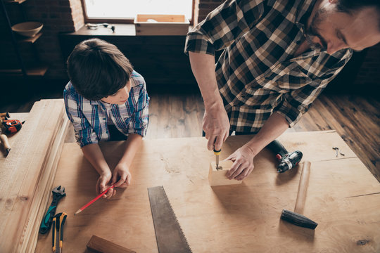 Top above high angle view photo of focused interested daddy papa kid family activity creative workshop interior industrial touch wood hardwood checkered shirt clothing indoors