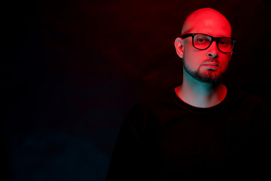 Attractive bald man with beard in glasses on neon light background
