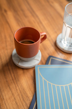 Mug of coffee on marble coaster on wood table