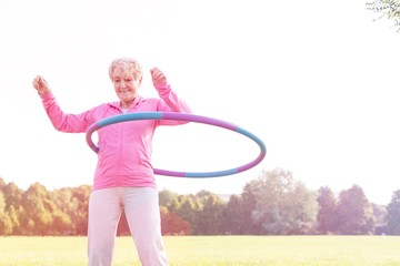 Senior woman doing gymnastic with hula hoop in park