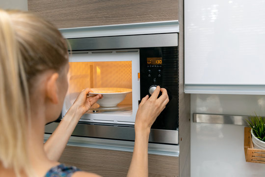 woman warm up the food in microwave oven at home