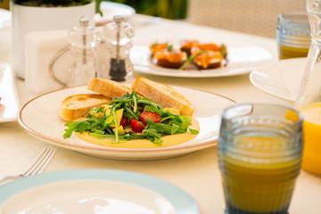 Bruschetta lying on plate near arugula and avocado salad