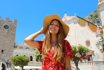 Summer holiday in Italy. Portrait of young woman with straw hat and red dress with Taormina village on the background, Sicily, Italy. Fototapete
