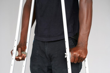 Hand african man on crutches on a gray background. Close-up man walking with crutches.