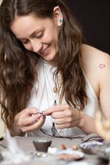Smiling artisan woman making handmade gemstone jewelry