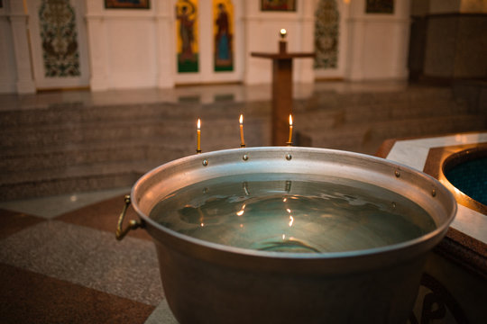 Infant baptism. Preparation for the baptism of children. container with water. burning candle fire