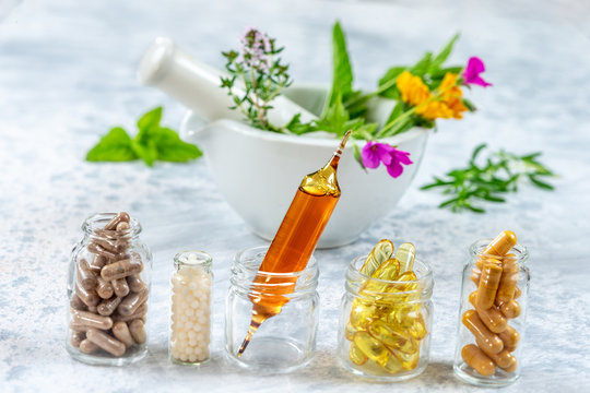 Herbal supplements and vitamins on wooden tray , decorated with colorfull medicinal flowers and herbs blurry wooden background