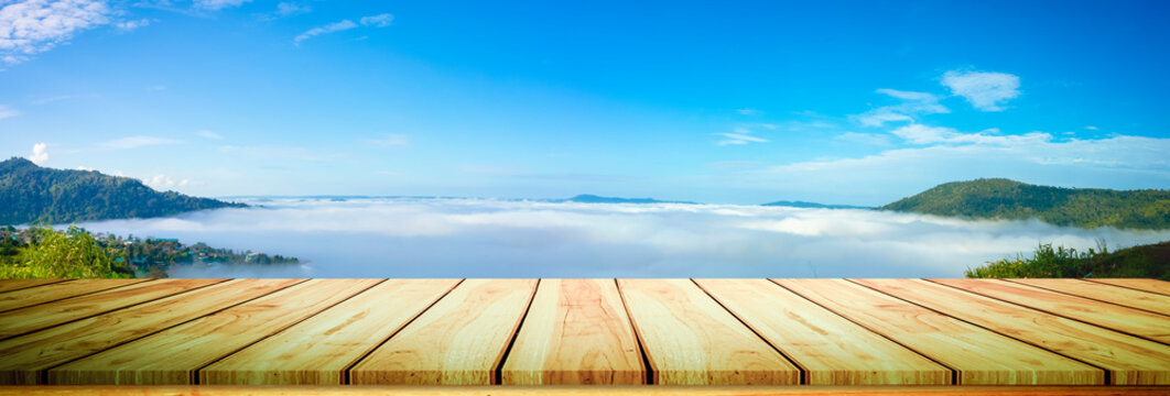 panorama image of wood table and mountain with Bule sky and could background