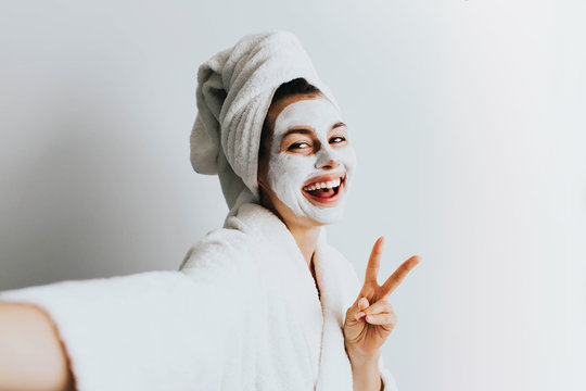 Self portrait of charming, stylish, pretty, model after bath wrapped in towel shooting selfie on front camera applying using face mask for her dry, oiled, sensual face skin, enjoying procedure