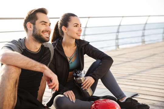 Cheerful young sporty couple sitting on a fitness mat