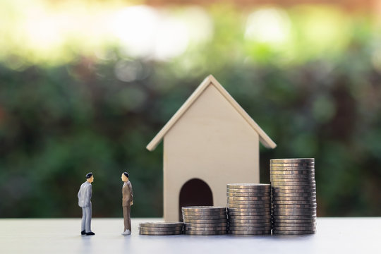 Property concept. Negotiating, trading or renting accommodation between brokers and customers. Two businessman miniature discussing about real estate price near stack of coins and a small house model.