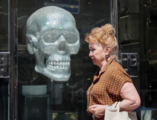 A woman walks in front of a shop window on a hot summer day in central Kiev