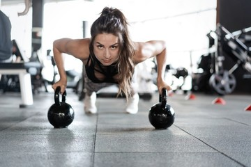 Sportive woman doing push-ups in the gym using kettlebells.