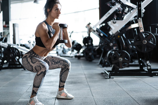 Athletic young woman fitness model doing squats exercise, concept sport healthy lifestyle.