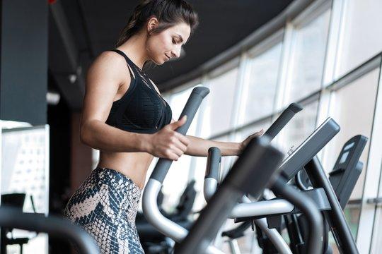 Beautiful gym woman exercising on a cardio machine smiling.
