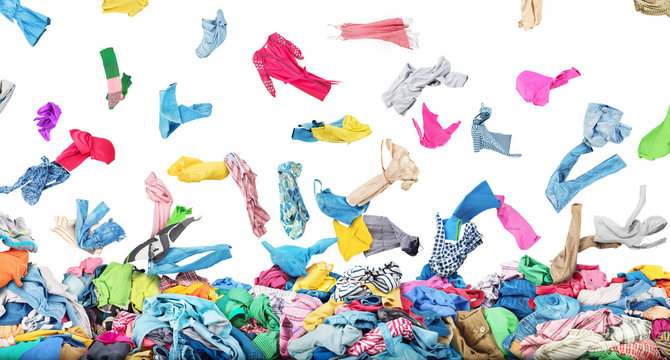 Sale concept. Separate clothing falling at the big pile of clothes on a white background. Donation