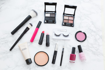 Variety of cosmetics arranged on white surface