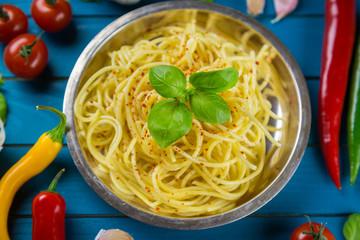 Metal plate of cooked Italian spaghetti pasta aglio olio e peperoncino