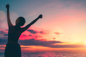 Happy woman standing arms outstretched back and enjoy life on the beach at Sea, background sky sunset silhouette.