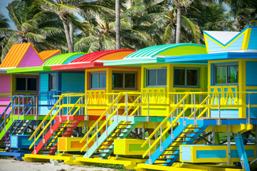 Colorful scenic morning view of brightly painted lifeguard towers with coconut palm trees on the South Beach promenade in Miami, Florida, USA Wall mural