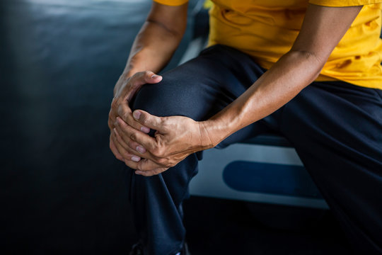Senior asian sport man injury knee pain  sitting on treadmill in fitness gym . aged  suffering from Arthritis elder male exercising , workout, training ,healthy ,Retirement ,older, close up