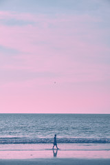 Foto op Plexiglas Purper Girl on the beach during sunset