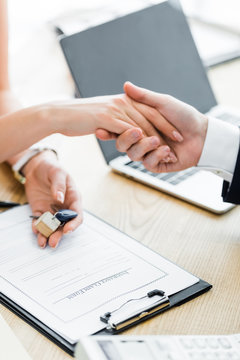 cropped view of woman holding keys in hand and shaking hands with realtor