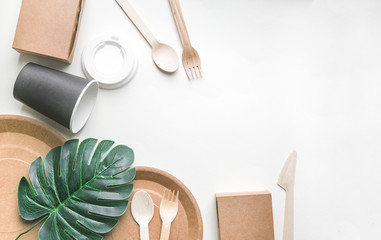 eco friendly disposable dishes made paper on white marble background. Draped spoons, fork, knives,...