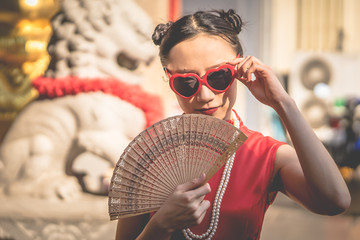 Chinese woman with sunglasses with vintage wooden fan for modern Chinese girl concept