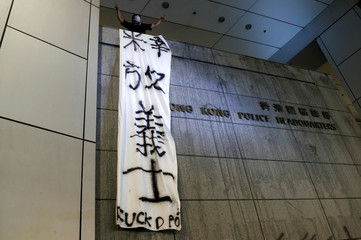 Protesters hang a banner as they siege police headquarters after a rally ahead of the G20 summit in Hong Kong