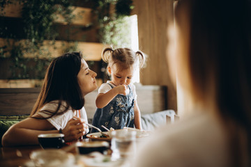 An attractive mother and her pretty girl, together with her girlfriend, rest in the cafe at the table, communicate with each other, eat and drink. beautiful woman with a child on holiday at restaurant