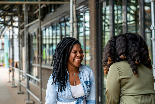Woman with dreadlocks smiling at friend