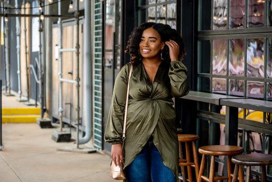Portrait of woman in green shiny tunic standing on sidewalk