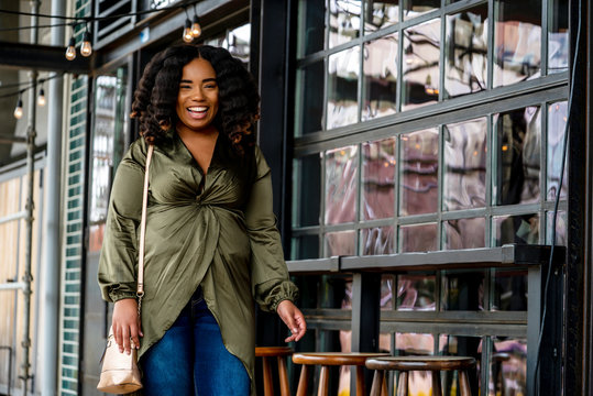 Portrait of woman laughing next to outdoor seating