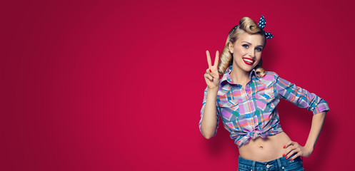 Photo of happy woman, showing two fingers or victory gesture, pinup style, over dark red color background