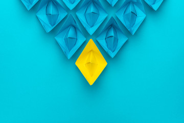 yellow paper ship ahead of blue ones leadership concept over blue background. top view of race with yellow winning paper ship metaphor. minimalist conceptual image of leadership