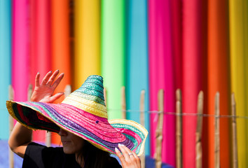 A reveller wears a rainbow coloured hat at Glastonbury Festival at Worthy farm in Somerset