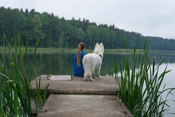 Woman and dog looking at the lake