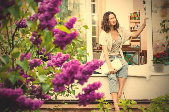 woman with book on window sill in garden