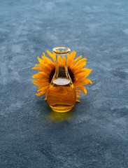 Sunflower oil in the carafe with sunflower blossom behind the bottle
