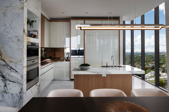 Miami Apartment Kitchen with floor to ceiling windows overlooking city.