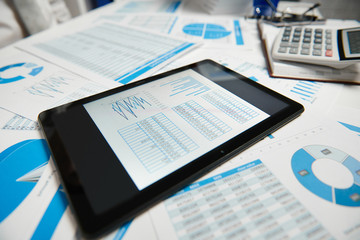 Office workspace for business. Tablet pc and reports. Table closeup. Business financial accounting...