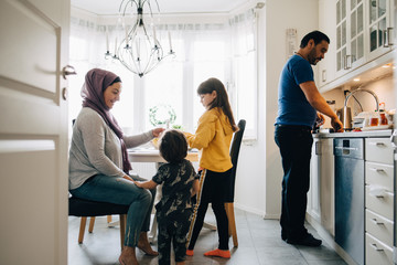 Woman sitting with children while man washing utensils in kitchen at home